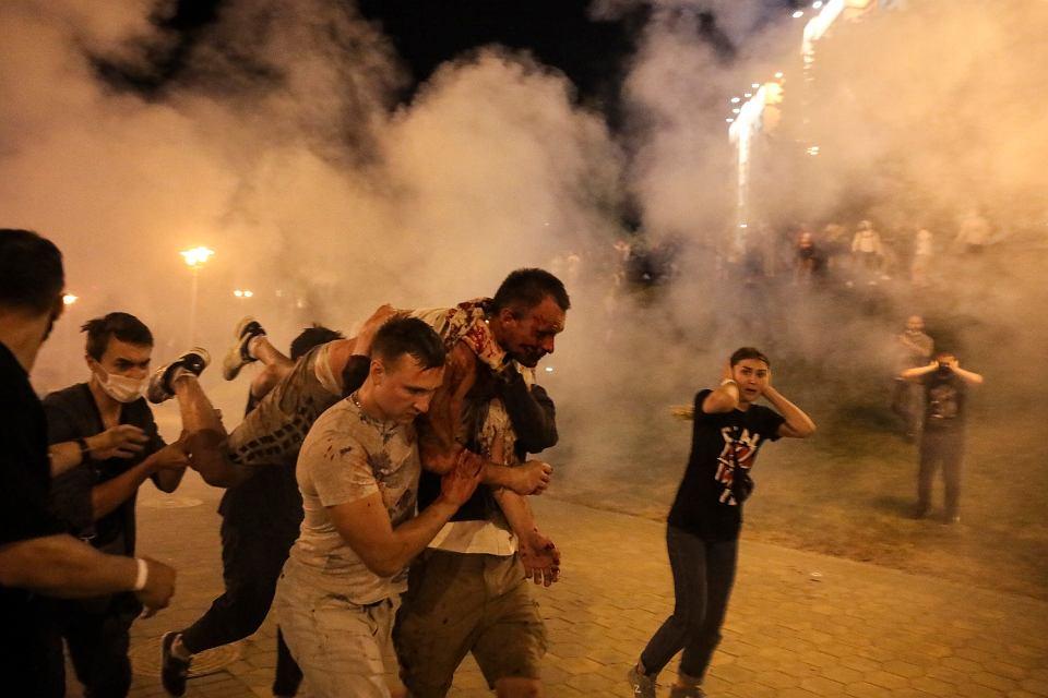 Protestujący niosą rannego mężczyznę podczas starć z policją po sfałszowaniu przez Aleksandra Łukaszenkę wyborów prezydenckich. Mińsk, 10 sierpnia 2020 r.