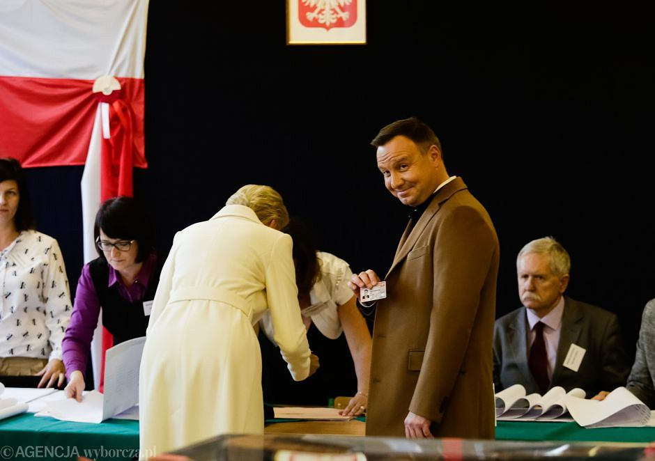 Prezydent RP Andrzej Duda pokazuje dowód osobisty podczas głosowania w wyborach samorządowych 2018 r. Krakowie