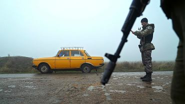 Ukraińscy policjanci sprawdzają wjeżdżających na punkcie kontrolnym w okolicach Berdiańska we wschodniej Ukrainie.