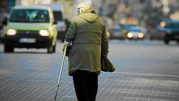 Starszy człowiek przechodzi przez ulicę w Łodzi.