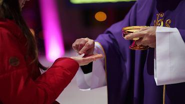 Ksiądz podaje komunię wiernej