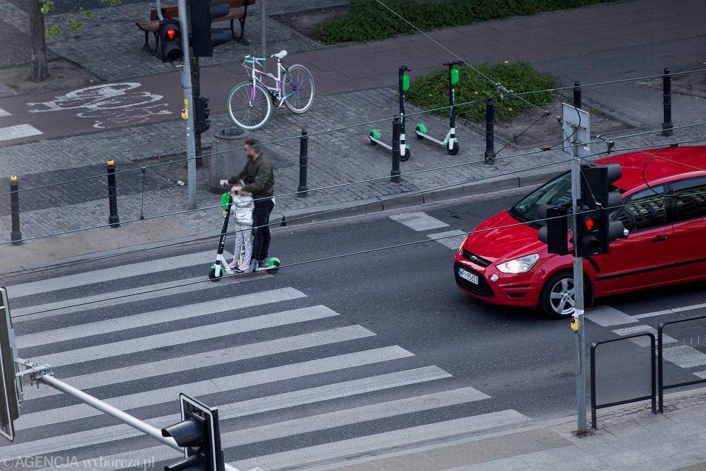 Użytkownik hulajnogi Lime jeździ z dzieckiem po ulicy
