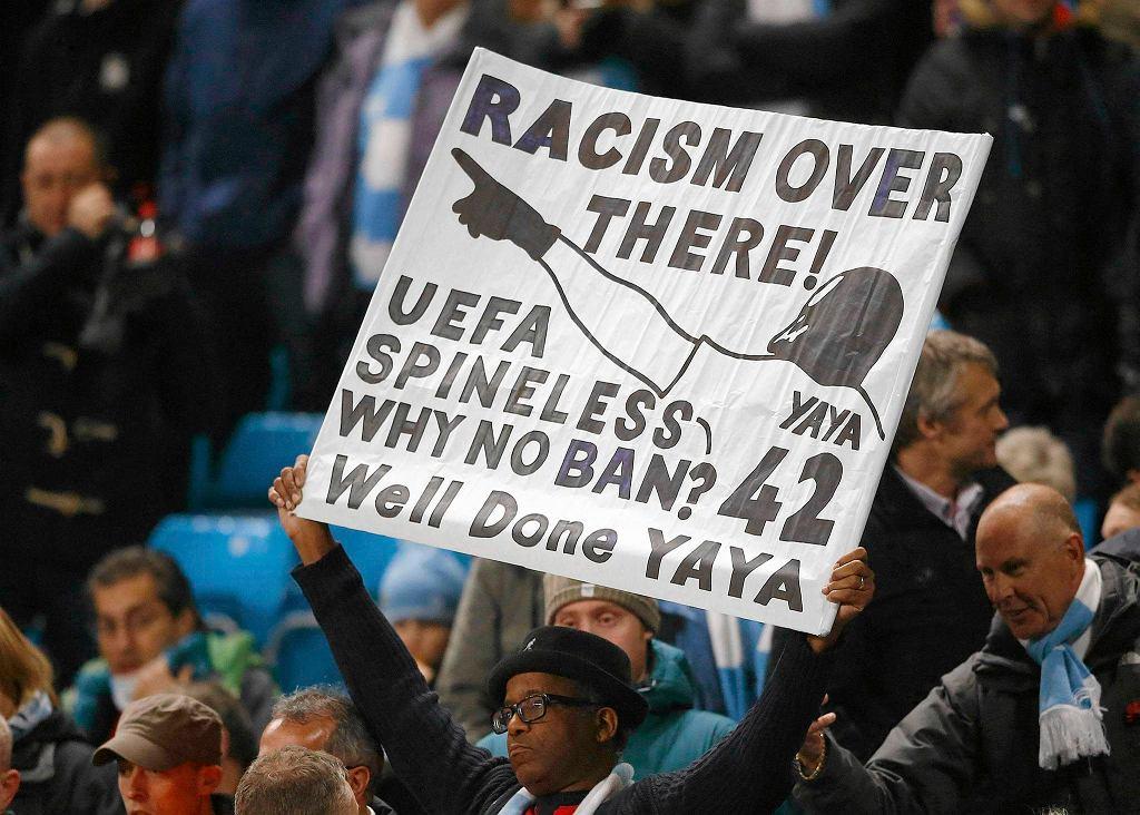 Fan trzyma w rękach baner potępiający rasizm na stadionach w Rosji i domagający się od władz piłkarskich reakcji.