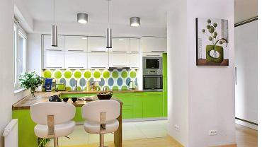 <B>Wygląda na to, że zabudowa w jednej barwie nieco sięnamznudziła. Projektanci proponują więc kuchnie zaaranżowane w dwóch kolorach. Nie są monotonne, a jednocześnie nie nazbyt dynamiczne. Powinny więc zadowolić różne gusta.</B>  <BR />Właściciele tego mieszkania lubią intensywne barwy, dlatego ich wnętrza, łącznie z otwartą kuchnią, pulsują kolorami. Na fronty kuchennych mebli, zrobionych z lakierowanej na wysoki połysk płytyMDF, wybrali żywą zieleń (szafki dolne) oraz łagodzącą ją biel (górne). Blat roboczy, połączony z barkiem-stołem, został wykonany zolejowanego klejonego drewna dębu. Podłogę przy szafkach wykończono płytami polerowanego gresu. Sąsiaduje on z posadzką z prasowanego bambusa w słomkowym odcieniu, którą ułożono w pozostałych częściach mieszkania.