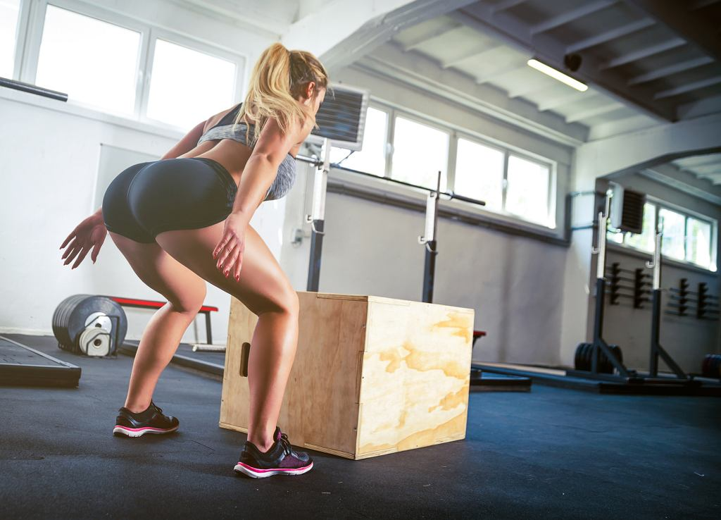 Fitness woman jumping on box training at gym