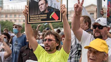 Mężczyzna trzyma plakat z portretem Aleksieja Nawalnego z podpisem: 'Nawalny został otruty, wiemy, kto jest winny, Aleksiej musisz żyć', podczas protestu w Chabarowsku w Rosji