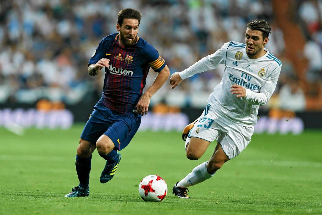 Barcelona's Lionel Messi, left, challenges Real Madrid's Mateo Kovacic