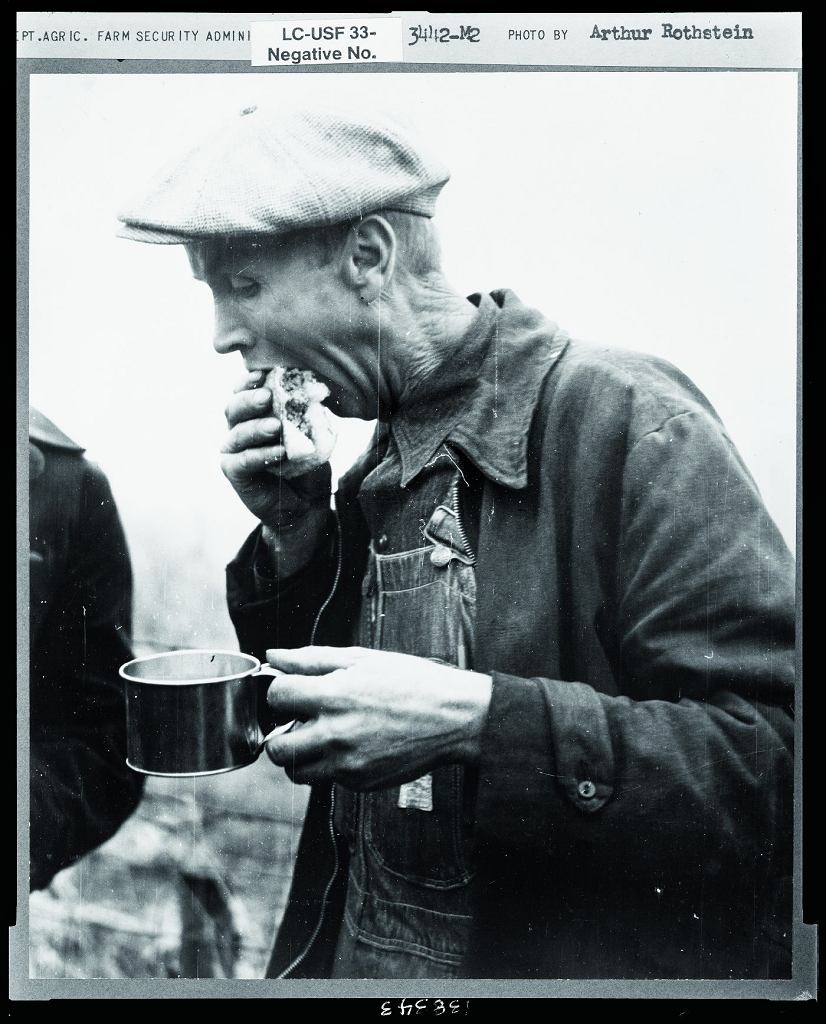 Farmer jedzący hamburgera podczas konkursu łuskania kukurydzy (Iowa, Stany Zjednoczone, 1939 r.)