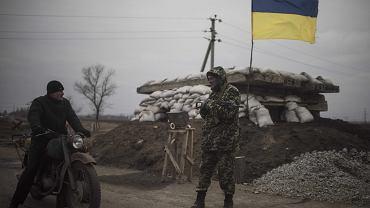 Ukraiński żołnierz rozmawia z mieszkańcem przy punkcie kontrolnym w pobliżu miejscowości Chermalyk