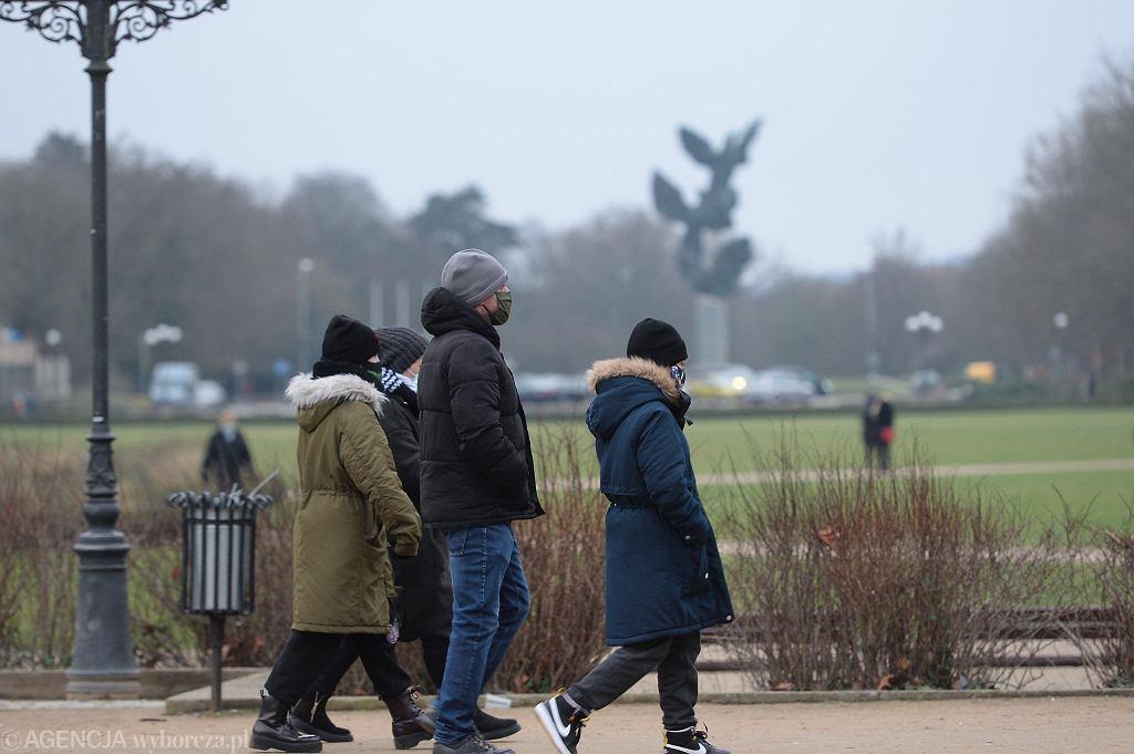 Słoneczny (momentami) drugi dzień świąt Bożego Narodzenia nakłonił całe rodziny do spaceru na Jasnych Błoniach w Szczecinie. To jedno z miejsc, gdzie - mimo obostrzeń związanych z pandemią koronawirusa - nie trzeba nosić maseczek. Rządowe rozporządzenie z 26 listopada 2020 r. stanowi, że nie ma obowiązku ich zakładania w obrębie parków, zieleńców, ogrodów botanicznych, ogrodów zabytkowych, rodzinnych ogródków działkowych i na plażach. Co ciekawe, z tego samego rozporządzenia wynika, że noszenie maseczek zakrywających usta i nos jest obowiązkowe na cmentarzach, promenadach i bulwarach. Czyli szczecinianie, którzy spacerowali dziś np. nad Odrą na Łasztowni, powinni maseczek używać.