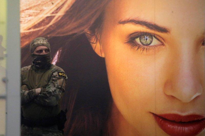 Funkcjonariusz FSB na tle reklamy szwedzkich kosmetyków przed budynkiem centrali w Moskwie