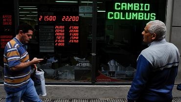 Ludzie przechodzący ulicą obok kantoru wymiany walut w Buenos Aires w Argentynie