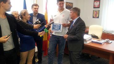Robert Urbanek odbiera nagrodę od marszałka Witolda Stępnia