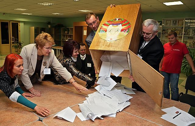 Opróżnianie urny wyborczej w jednym z lokali w Mińsku