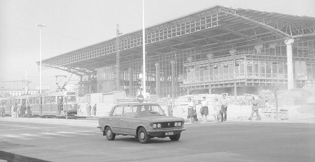 Fragment szkieletu konstrukcji Dworca podczas ostatniej fazy budowy - widok od strony skrzyżowania Al. Jerozolimskich z ul. Emilii Plater. Na jezdni widoczny tramwaj Konstal 13N linii 24 nr boczny 524 i samochód Fiat 125p.  Data wydarzenia: 1975-05-01 - 1975-07-18