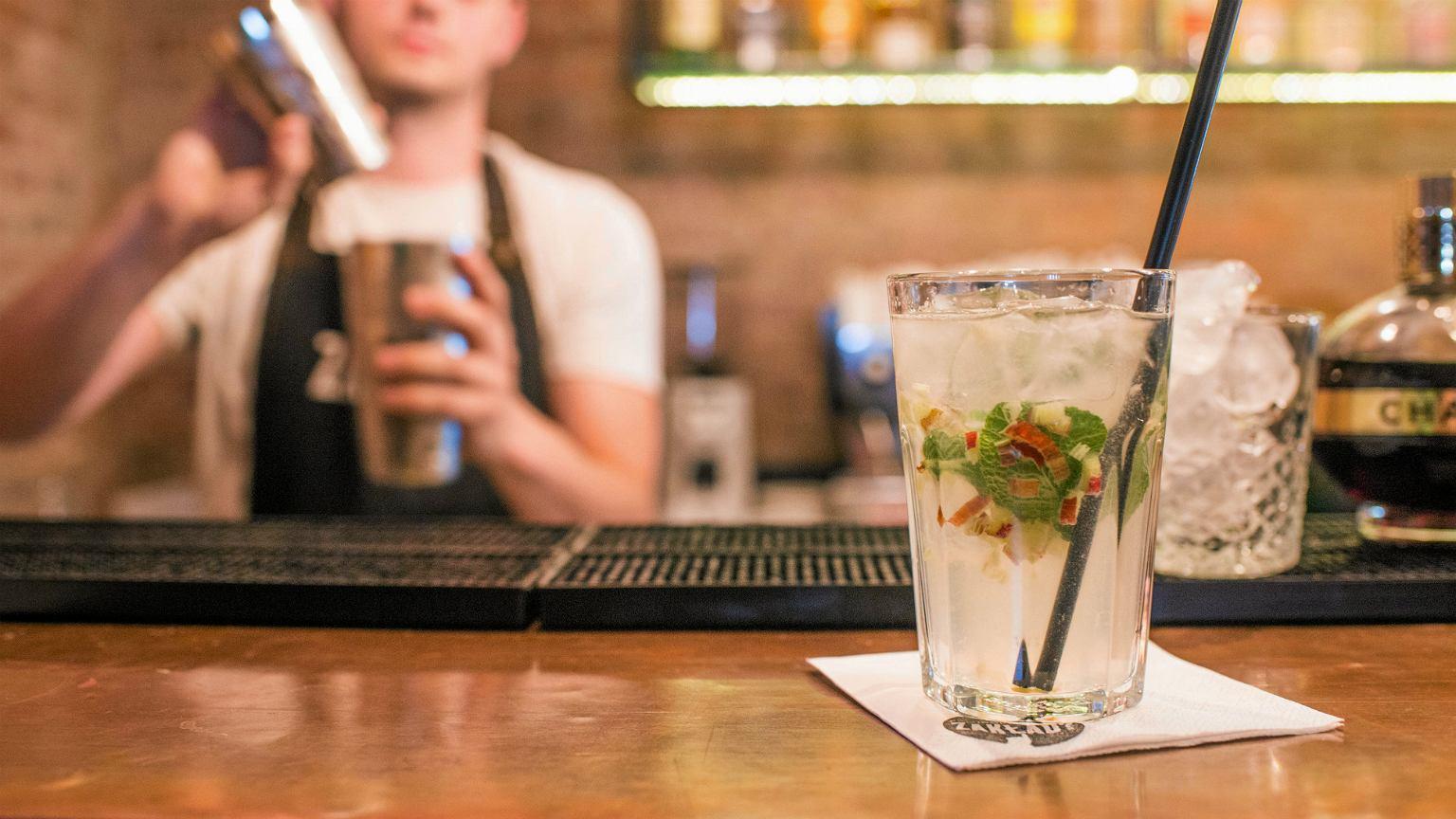 Bar, w tle barman przyrządzający koktajl