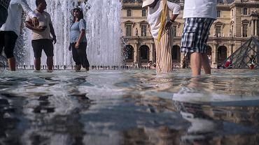 Turyści i paryżanie szukają ochłody w pobliżu Luwru. Paryż, 24 lipca 2019 r.