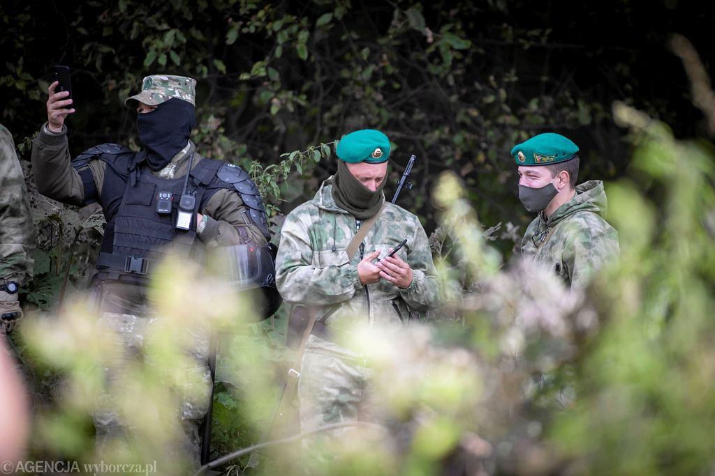 Białoruscy pogranicznicy i prawdopodobnie funkcjonariusze jednostek specjalnych, pilnujący grupy migrantów opodal Usnarza Górnego
