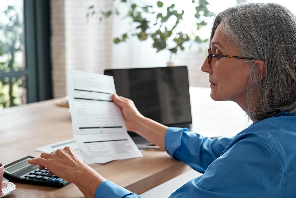 ESenior,Mature,Business,Woman,Holding,Paper,Bill,Using,Calculator,,Old. Emeryt, emerytura