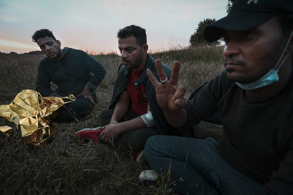 Mohammed (l), Safaa (c) and Faysal (r) are seen exhausted in a field near the border on 14 August, 2021 in Minkowce, Poland. Faysal attempts to explain to a reporter they have been sent over the border and returned to Belarus multiple times.