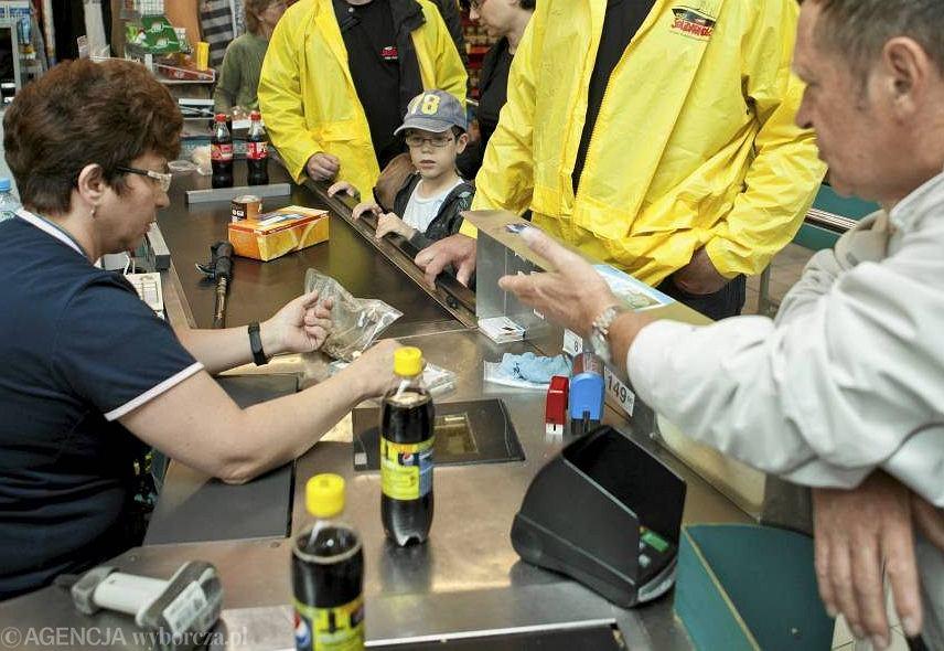 Kasjerka wydająca resztę klientowi w sklepie wielkopowierzchniowym.