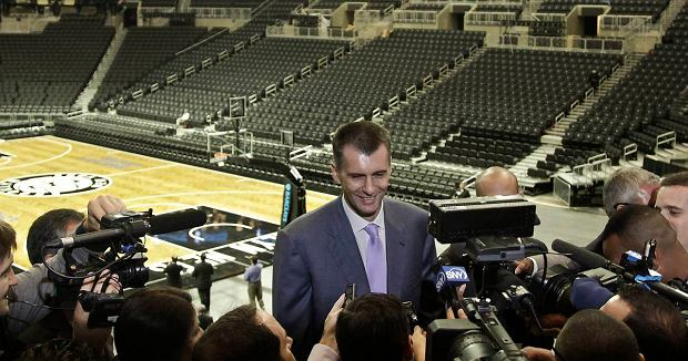 Brooklyn Nets owner Mikhail Prokhorov, center, speaks with reporters after a ribbon cutting ceremony at the Barclays Center, the NBA basketball team's new home,  Friday, Sept. 21, 2012 in New York.  After decades without a professional sports team, New York City's ascendant borough hit the major leagues again on Friday with the opening of the Brooklyn Nets' new arena.  (AP Photo/Bebeto Matthews)