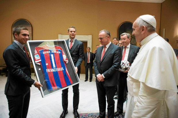 Bayern Munich soccer players give a team jersey to Pope Francis before his weekly audience in Saint Peter's Square at the Vatican October 22, 2014. REUTERS/Osservatore Romano (VATICAN - Tags: RELIGION SPORT SOCCER) ATTENTION EDITORS - THIS PICTURE WAS PROVIDED BY A THIRD PARTY. FOR EDITORIAL USE ONLY. NOT FOR SALE FOR MARKETING OR ADVERTISING CAMPAIGNS. THIS PICTURE IS DISTRIBUTED EXACTLY AS RECEIVED BY REUTERS, AS A SERVICE TO CLIENTS. NO SALES. NO ARCHIVES SLOWA KLUCZOWE: :rel:d:bm:GF2EAAM0OH401