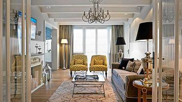 Salon ma na ogół reprezentacyjny charakter. Meble ustawia się zgodnie z zasadami symetrii. Przytulności dodają wnętrzu tkaniny - zasłony, dywany, poduszki na kanapie i fotelach. Całość jest utrzymana w neutralnej, spokojnej kolorystyce.