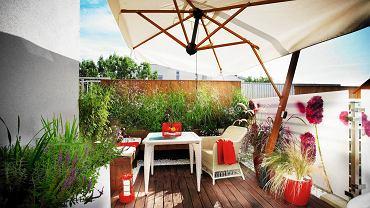 <B>Wystarczyły dwa tygodnie, by taras z betonu i stali na dachu budynku w środku miasta zmienił się w cichy, idylliczny zakątek, w którym gospodarze czują się jak na wiejskiej łące. Skąd takie wrażenie? Wywołują je użyte materiały, zwłaszcza naturalne drewno, oraz doniczkowe rabatki skomponowane z kwitnących wśród traw delikatnych roślin.</B> <BR /> METAMORFOZA TARASU.  Płotek zasłania widoczną z tarasu konstrukcję dachu i zapewnia bezpieczeństwo. Zrobiono go z thermojesionu (dzięki obróbce w wysokiej temperaturze drewno ciemnieje i nabiera odporności). <BR /> Meble ze sztucznego rattanu są odporne na deszcz i śnieg, dzięki czemu nie trzeba ich przenosić na zimę do mieszkania. Rozłożony w upalne dni parasol daje upragniony cień. <BR />  Na ekranie z pleksi nadrukowano bordowe  kwiaty zawciągu nadmorskiego. Ekran nie tylko zdobi taras, ale również chroni domowników przed wzrokiem sąsiadów i zasłania widok na miasto.