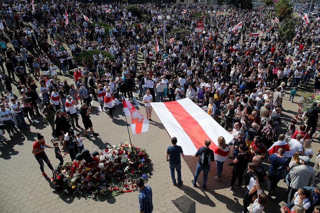 Białorusini demonstrujący w dniu pogrzebu Aleksandra Tarajkouskiego
