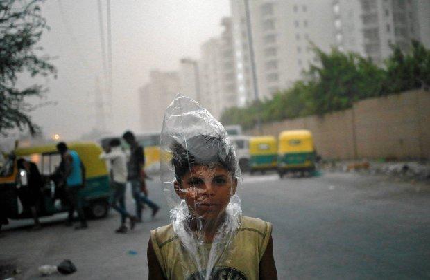 Młody chłopiec z plastikową torbą na głowie, mającą chronić go przed zanieczyszczonym powietrzem w Dehli, Indie. 23 maja.