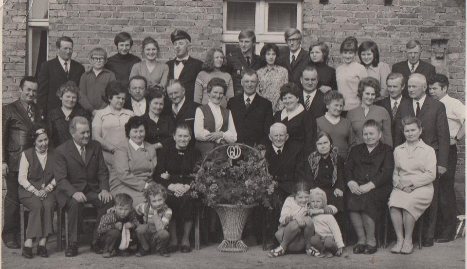 60 rocznica pożycia małżeńskiego dziadków-rodziców Bolesław Budzińskiego. Pierwszy z lewej stoi tata, poniżej siedzi mama. Ja to ten blondynek po lewej stronie kosza z kwiatami z podpartą głową i spodniami na szelkach. Obok mój kuzyn, później wieloletni sołtys w Konojadzie. Połowa lat 70-tych. Dom dziadków w Konojadzie.