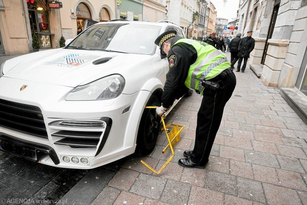 Strażnicy miejscy nie mogą znaleźć odpowiednio dużej blokady na koło luksusowego porsche cayenne, Kraków 2013.
