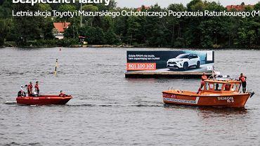 Akcja  'Bezpieczne Mazury'. Platforma ze stacją pogodową i reklamą samochodu ustawiona na szlaku Wielkich Jezior Mazurskich - pierwsza wersja