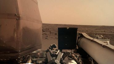Zdjęcie, które dotarło na Ziemię we wtorek nad ranem naszego czasu. Wykonała je kamera zamontowana na robotycznym ramieniu (jeszcze nie rozprostowanym) sondy InSight. Na pierwszym planie korpus sondy, a w tle płaska aż po horyzont równina Elysium Planitia, na której wylądowała sonda