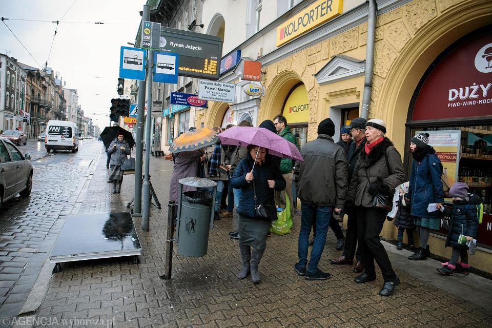 Rynek Jeżycki. Koalicja Odnawiamy Jeżyce domagając się wygodnego przystanku wiedeńskiego, podsuwa podest pod drzwi tramwaju, by pomóc pasażerom we wsiadaniu i wysiadaniu