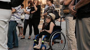 Pod hasłem 'O godne życie i prawa osób niepełnosprawnych oraz realizację postanowień Konwencji Praw Osób Niepełnosprawnych' protestowało w poniedziałek na pl. Teatralnym w Lublinie ok. 100 osób. Protestujący domagali się spełnienia przez rządzących 12 postulatów RON. RON, czyli Środowisko Rodziców Osób Niepełnosprawnych, sprzeciwia się sytuacji, w której po trzech latach rządów PiS społeczeństwo korzysta z programów wsparcia, zaś osoby z niepełnosprawnością otrzymują 'głodowe świadczenia'. Środowisko utworzyło listę postulatów. Domaga się stworzenia przez rządzących modelu wsparcia, zapewniającego osobom niepełnosprawnym pełną autonomię, niezależność oraz możliwość samodzielnego życia w społeczeństwie. Ale lista to za mało. RON organizuje demonstracje, które są kontynuacją niedawnych protestów rodziców osób niepełnosprawnych w Sejmie. - Jestem tu, żeby wesprzeć inne osoby niepełnosprawne i żeby zaznaczyć, że od czasu, kiedy odbył ostatni protest, nic się nie zmieniło - mówi Olga Żeligowska, która od urodzenia choruje na przepuklinę oponowo-rdzeniową i wodogłowie, porusza się na wózku. Uczestnicy demonstracji - osoby niepełnosprawne, ich opiekunowie, rodzice i osoby wspierające RON wspólnie zbierali podpisy pod petycją skierowaną do minister edukacji Anny Zalewskiej. Na miejscu pojawili się też przedstawiciele lubelskiego KOD-u. Mieli przy sobie transparenty z napisami 'Miarą człowieczeństwa jest troska o najsłabszych' i 'Popieramy postulaty osób z niepełnosprawnościami'. - Przyszłam tu dla mojego dziecka, które ma już 27 lat i jest niepełnosprawne w stopniu znacznym. Walczymy o spełnienie postulatów, których rząd nie chce realizować. Przede wszystkim jednak sprzeciwiamy się dyskryminacji dzieci niepełnosprawnych w wieku szkolnym - wyjaśnia Aneta Mielko, mama niepełnosprawnej Karoliny, mając na myśli rozporządzenie MEN, zgodnie z którym dzieci z niepełnosprawnością objęte nauczaniem indywidualnym od nowego roku nie mogą już chodzić do szkoły razem ze swoimi rówieśnik