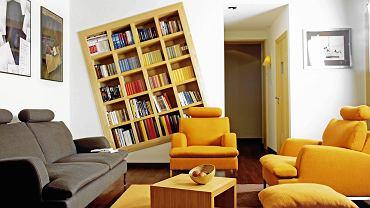 WNĘTRZA: półżartem<BR /> Prosty drewniany regał został wbudowany skosem w ścienną wnękę. Na takie nietypowe rozwiązanie zdecydowali się gospodarze, którzy do tradycyjnie urządzonego salonu chcieli wprowadzić nieco humoru.<BR /> Warto wiedzieć: światło do czytania Prawdziwy bibliofil nie obejdzie się bez wygodnego miejsca do czytania. Aranżując kącik, pamiętajmy o dobrym oświetleniu. W pomieszczeniu, w którym czytamy, jest potrzebne łagodne światło ogólne; bezpośrednio na książkę powinno natomiast padać dodatkowe, lekko rozproszone światło punktowe. W zależności od wystroju wnętrza kącik możemy oświetlić lampą podłogową lub biurkową z regulowanym ramieniem i nieprzezroczystym abażurem. Przydadzą się również halogenowe punkty, zainstalowane np. w suficie nad półkami, które oświetlą księgozbiór i ułatwią wyszukiwanie potrzebnych książek. Wybierając źródło światła, zdecydujmy się na dobrej jakości energooszczędne świetlówki lub LED-y.  Najkorzystniejsze dla naszych oczu jest światło o barwie zbliżonej do naturalnego (tzw. barwa dzienna) i o mocy 40-60 W.