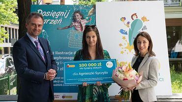 Czek na 100 tys. zł wręczają jurorzy: Arkadiusz Mierzwa i Agnieszka Karp-Szymańska, materiał promocyjny