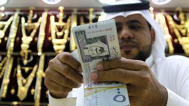 Saudyjczyk przelicza pieniądze w sklepie z biżuterią