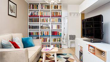 Właścicielka mieszkania uwielbia czytać, dlatego stworzono wysoki, pojemny regał aby pomieścić wszystkie książki. Dzięki wielobarwnym grzbietom stanowią one dodatkową dekorację i ożywiają stonowane wnętrze.