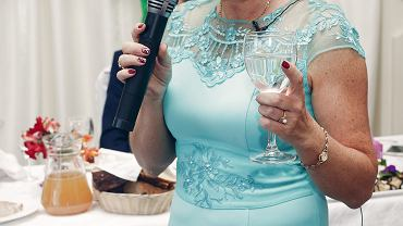 >Happy,Mother,In,Law,With,Champagne,In,Glass,Holding,Microphone