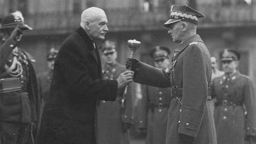 """10 listopada 1936 r., dziedziniec Zamku Królewskiego w Warszawie. W przeddzień 18. rocznicy odzyskania niepodległości prezydent Ignacy Mościcki awansował głównego inspektora sił zbrojnych Edwarda Rydza-Śmigłego o dwa stopnie wojskowe - najpierw mianował go generałem broni, a następnie wręczył buławę marszałkowską. Wielu piłsudczyków przyjęło to z niesmakiem, uważając, że na buławę zasłużył jedynie Piłsudski. Walery Sławek, który przegrał rywalizację o władzę, nazwał dzień nominacji Śmigłego """"najsmutniejszym w swoim życiu""""."""