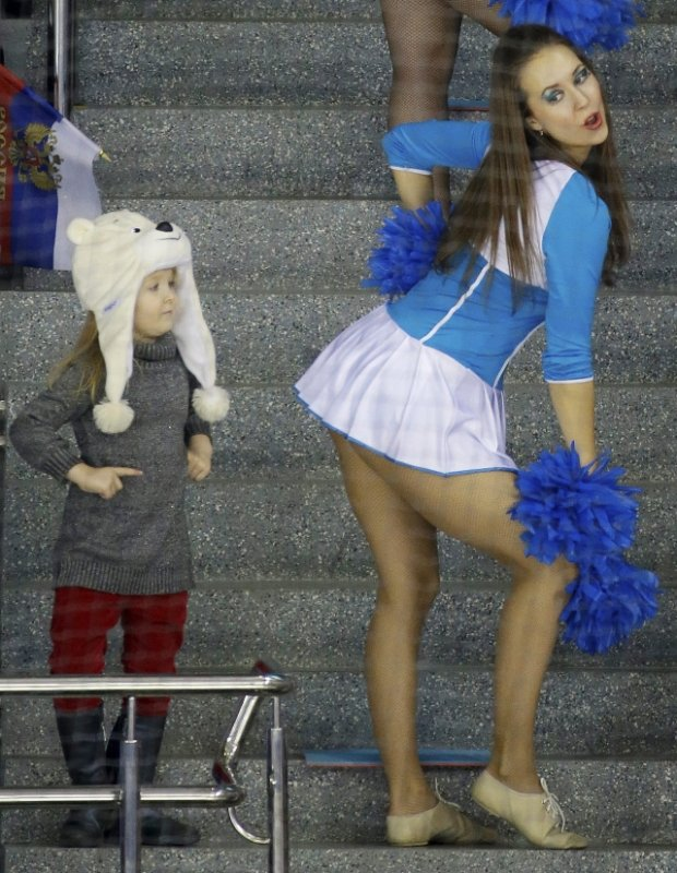 A young fan watches as a Sochi Olympic cheerleader performs during the game between Russia and Japan during 2014 Winter Olympics women's ice hockey match at Shayba Arena, Tuesday, Feb. 11, 2014, in Sochi, Russia. (AP Photo/Mark Humphrey)