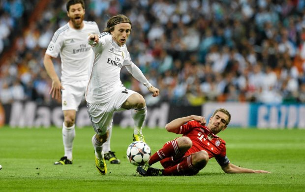 Real's Luka Modric, left, is challenged by Bayern's Philipp Lahm during a Champions League semifinal first leg soccer match between Real Madrid and Bayern Munich at the Santiago Bernabeu stadium in Madrid, Spain, Wednesday, April 23, 2014. (AP Photo/Paul White) SLOWA KLUCZOWE: XCHAMPIONSLEAGUEX