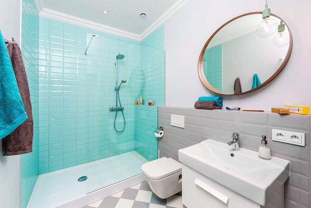 Błękitne płytki typu metro wyznaczają prysznic. W pozostałej części łazienki położono szare płytki.