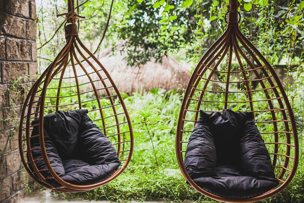 Huśtawka ogrodowa, która przypomina wiszący fotel.
