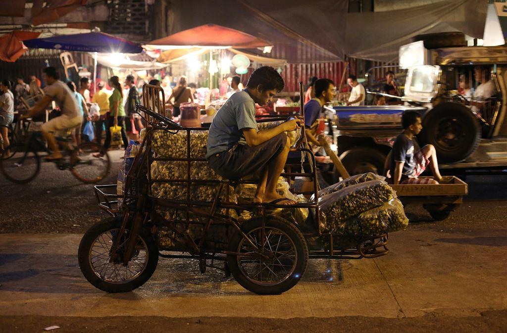 Pracownik czeka na dostawę warzyw, które później dostarczy na targowisko w stolicy Filipin, Manili