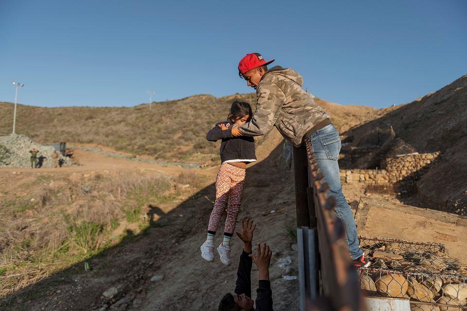 Migrant z Hondurasu przekazuje dziewczynkę jej ojcu po tym, jak ten przeskoczył mur graniczny, aby dostać się na stronę amerykańską do San Diego w Kalifornii z Tijuany w Meksyku, 2019 r.
