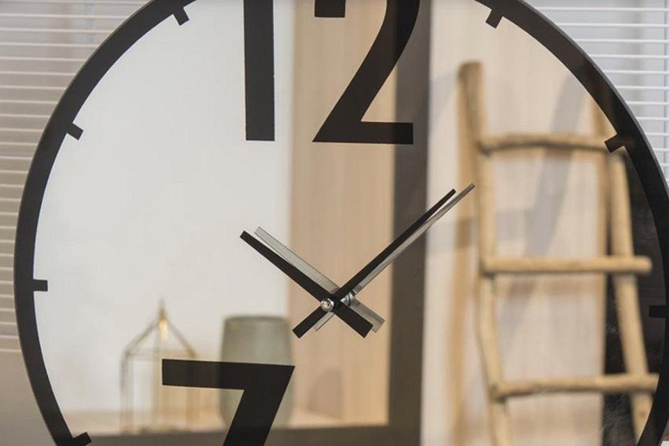 Zegar ścienny na lustrze.